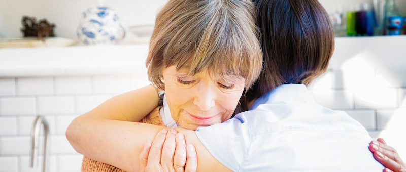 Senior mother hugs daughter while grieving, sad as she remembers her lost husband.